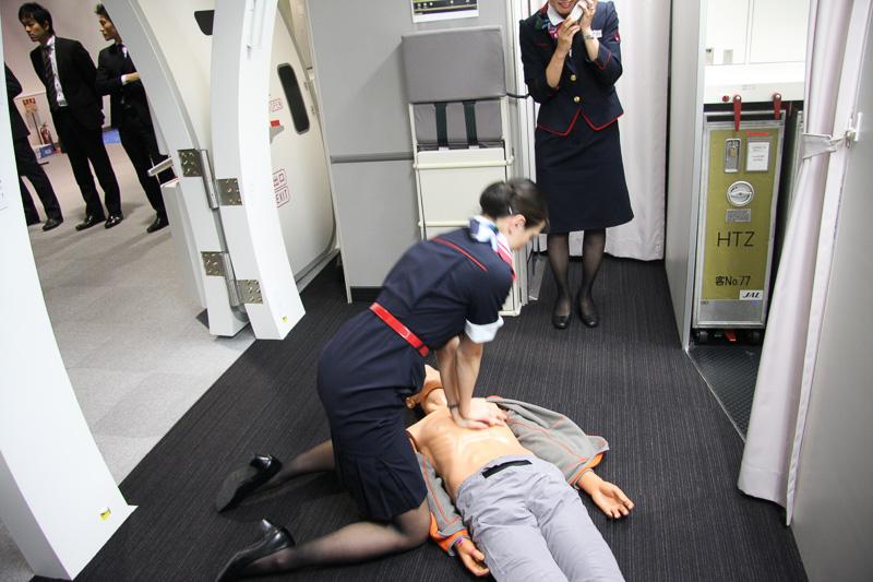 CAによるAEDの実演。突然の心臓停止となった乗客の命を守るべく、航空機にはAEDが搭載されている。もちろんCAはAEDの操作訓練を受けており、写真は心停止となった乗客に対応した状況。AEDのほか、手動式人工呼吸器、心肺マッサージ、気道確保などさまざまな手法で乗客の命を救っていく