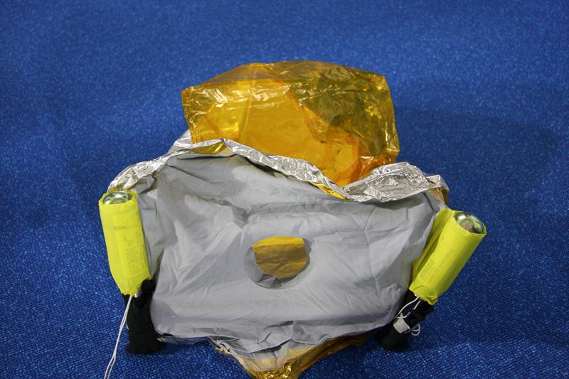 航空機に搭載されている防火防煙マスク。ひもをちぎり、もむようにして展開する。一般の乗客ではなく、CAなどが機内火災の際に使用する