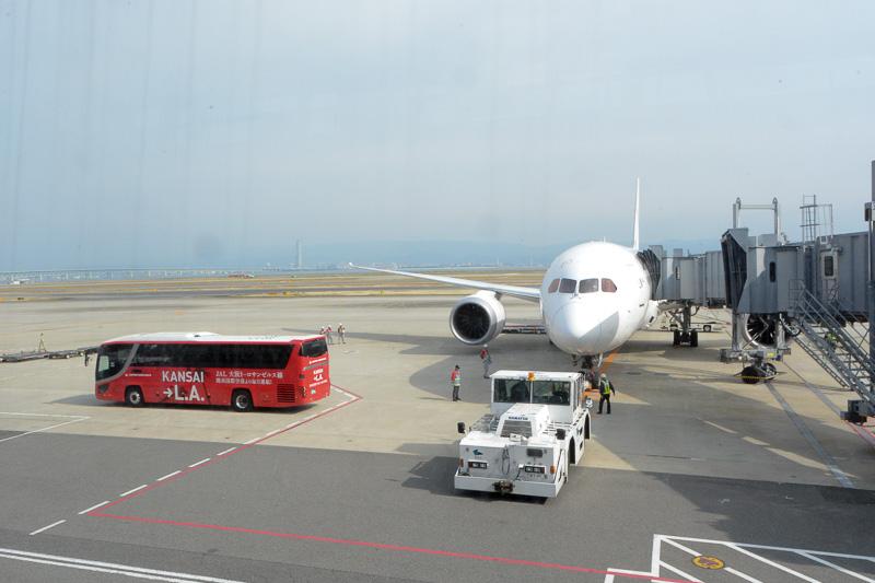 出発を待つJL60便のボーイング787型機。脇には就航記念ラッピングバスも待機