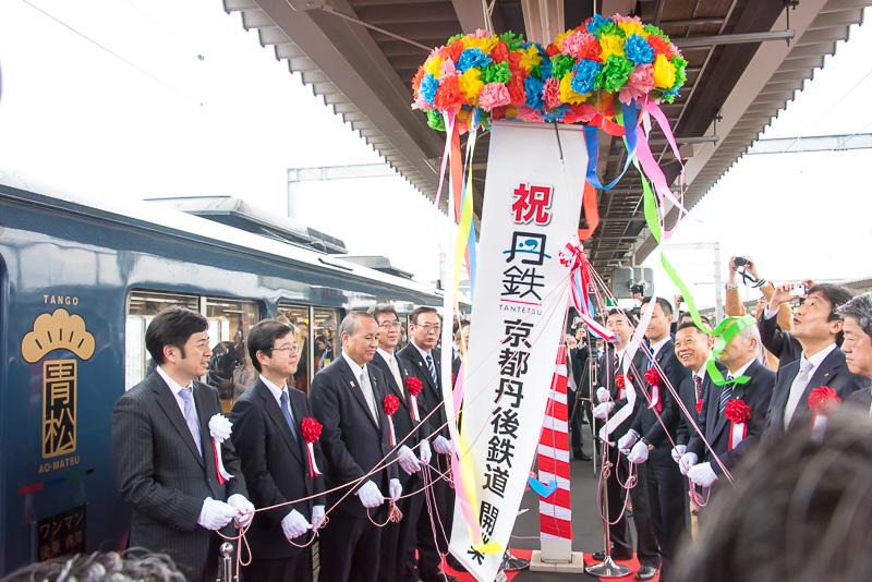 WILLER TRAINS 代表取締役 村瀬茂高氏(左)、国土交通省 鉄道事業課長 大石英一郎氏(左から2番目)ほか、関係者が参列し、福知山駅 京都丹後鉄道ホームで出発式が行われた。