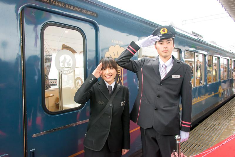 出発式は福知山駅14時59分発の天橋立駅行きカフェトレイン「あおまつ」を使用した列車で行われた。乗務した運転士の矢野裕城氏(右)とアテンダント 前田菜津美さん。制服はウィラーグループのイメージカラーであるピンクのラインが入ったものに変わった