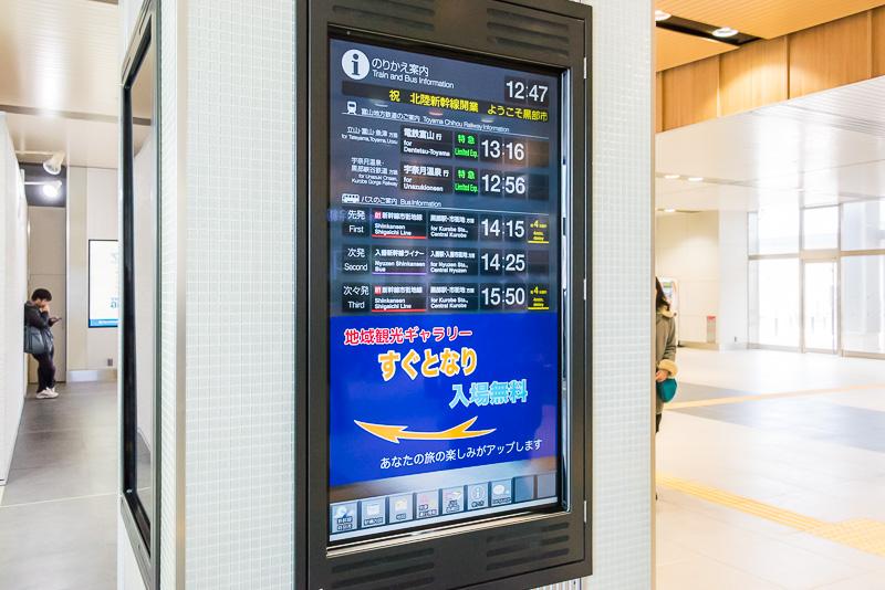 改札前の柱はデジタルサイネージになっており、富山地鉄やバスなどの時間が表示されている