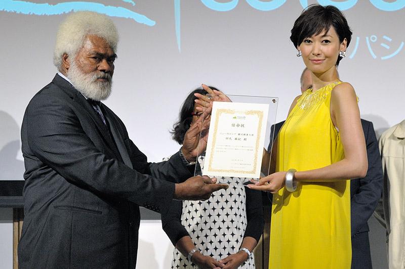 GIEロイヤリティ諸島観光局会長のワヌー氏から任命賞を授与される田丸さん