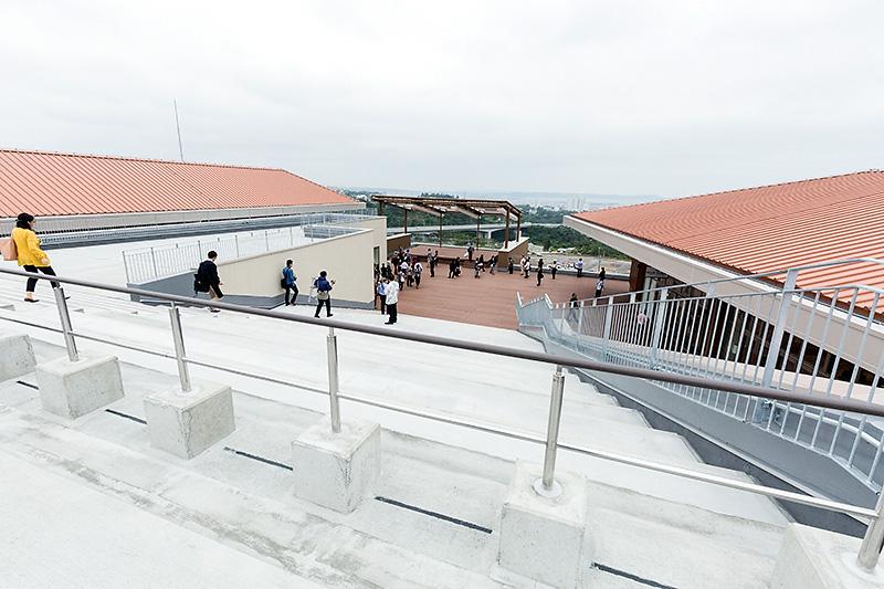 階段をさらに上って、屋上のオープンスペースから。奥には沖縄の海が遠望できる。右の建物が5階のレストランエリア、左に見えるのがイベントステージ