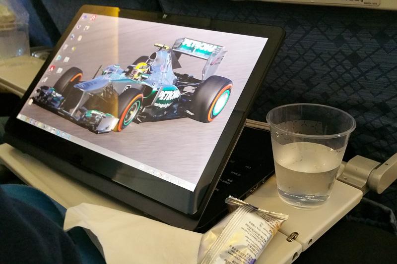 CA(客室乗務員)からもらった飲み物(といっても水だが)を飲みながらPCで資料を見るの図。最近のPCはこのように液晶が回転する2-in-1デバイスが増えてきており、あまり広くないエコノミークラスのシートでもこのように開くことができる