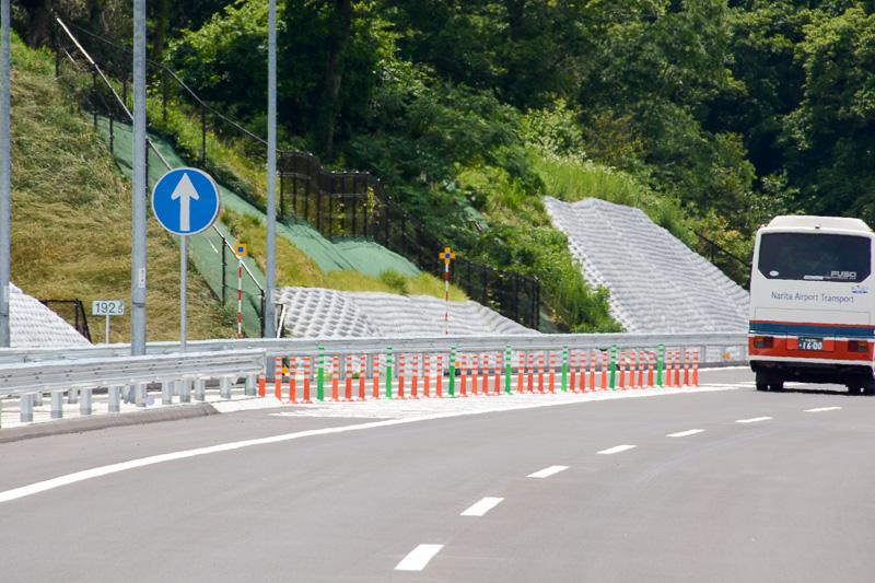 合流地点からの逆走を防ぐため、ゼブラ全域にラバーポールを設置。路面の大型矢印標識やガードレールの高輝度矢印板などを設置して対策している