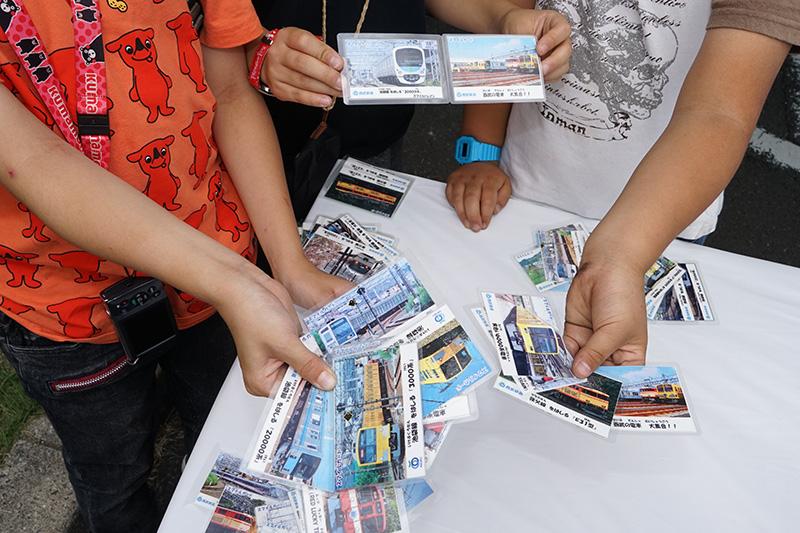 各所でキッズ向けに無料で配られる職員手作りの電車カード。集めている子供たちによると、すでにレアなカードもあるらしい。自慢のカードを見せてくれた