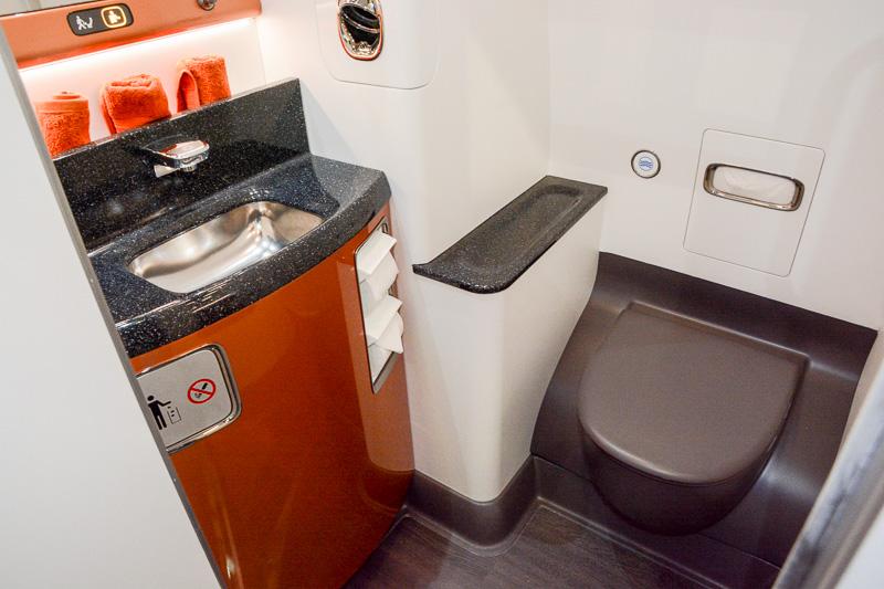 ビジネスクラス最前列席とその先のトイレ。右側の壁の部分に洗面台。足元の先には実は便座がある