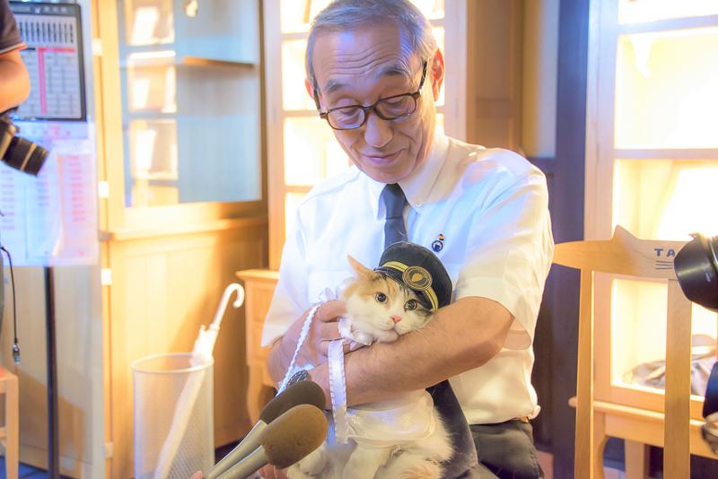 「ニタマ」を抱いてインタビューに応じる小嶋氏