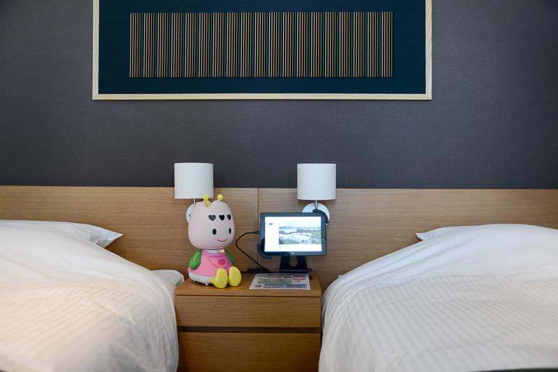 部屋のベッドサイドにはロボットの「ちゅーりーちゃん」とWindowsタブレット
