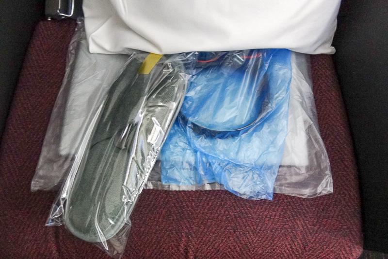 搭乗時に座席にはスリットとヘッドフォン、ブランケット、枕が用意されていた