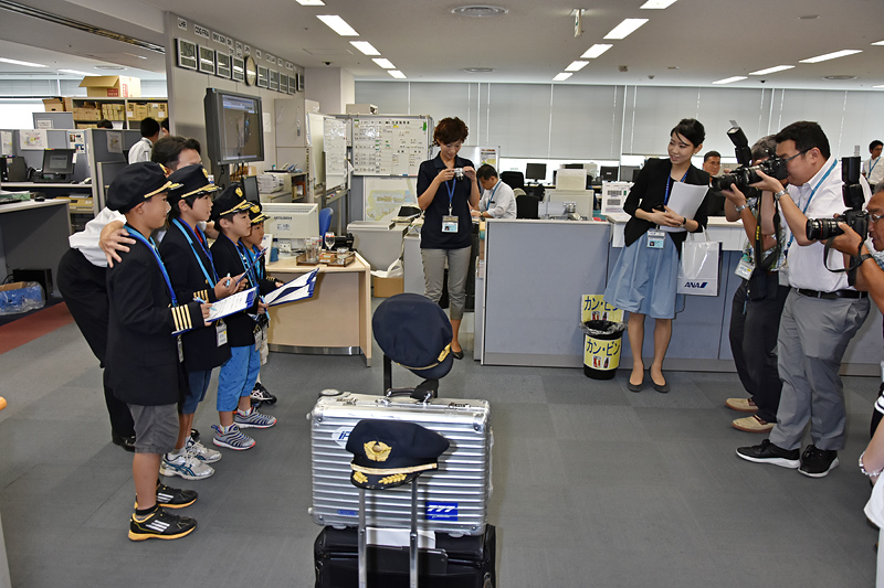 報道陣のカメラに囲まれ、硬くなっている子供たちと記念撮影
