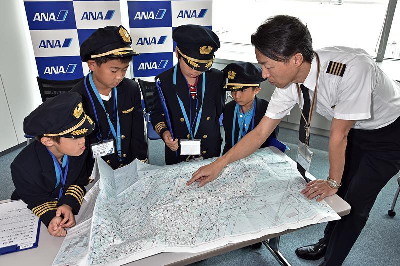 エンルートチャートを説明する久保機長。英語表記なので子供たちには少し難しい