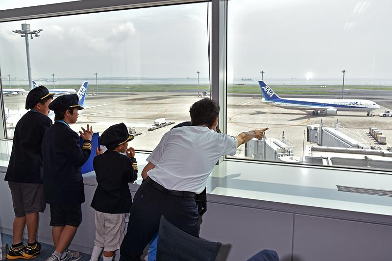 エアポートチャートで、今、自分たちがいる場所を説明する久保機長。窓から見える駐機場番号を「ほら、64番って見える?」と、チャートと照らし合わせながら説明する