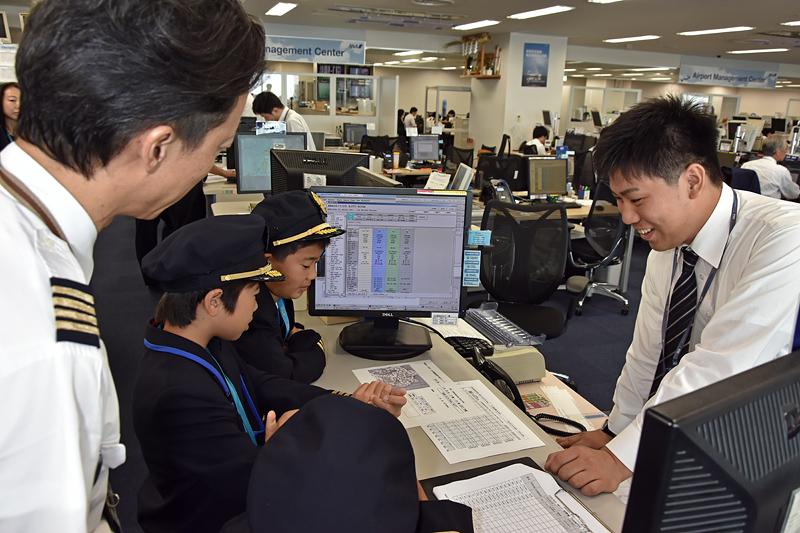 キッズレポーターたちは、パイロットをサポートする運航支援カウンターでも話を聞いた。火山噴煙拡散予想チャートを例に、さまざまな事に注意しなければいけないということを学んだ