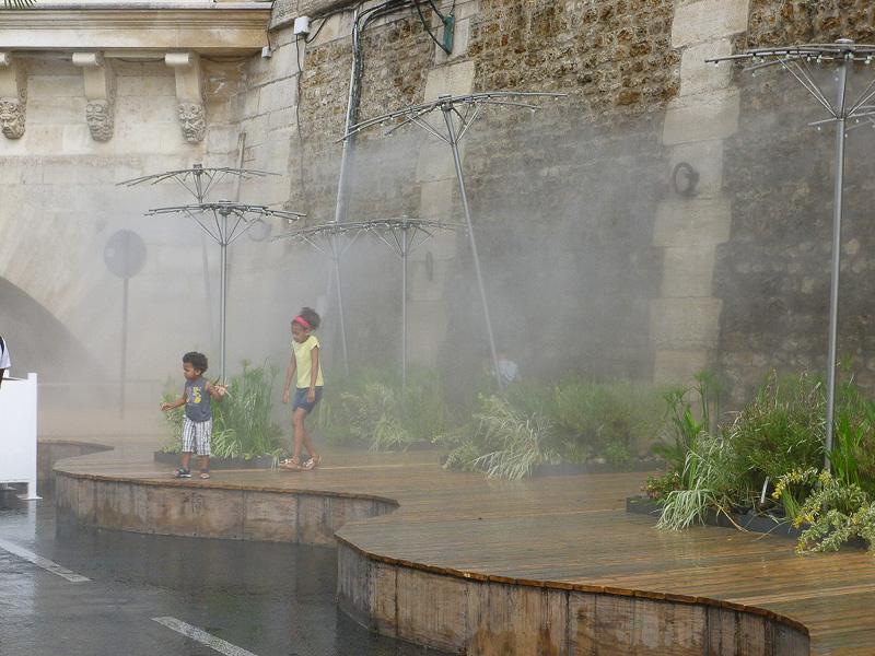霧の出るシャワーの下では子供たちが大はしゃぎ