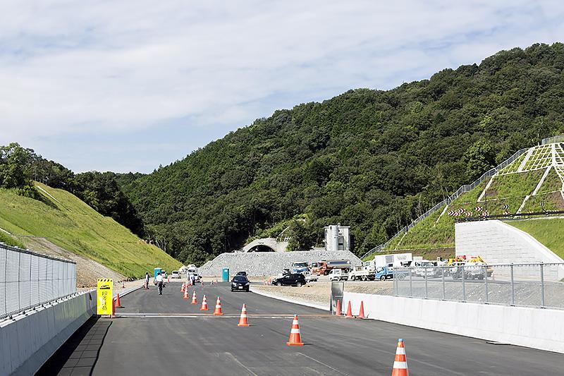 残る区間は2016年度中の開通を目指して工事が進む。写真奥に見える安上岩出トンネルは掘削を終え内部工事が進められている