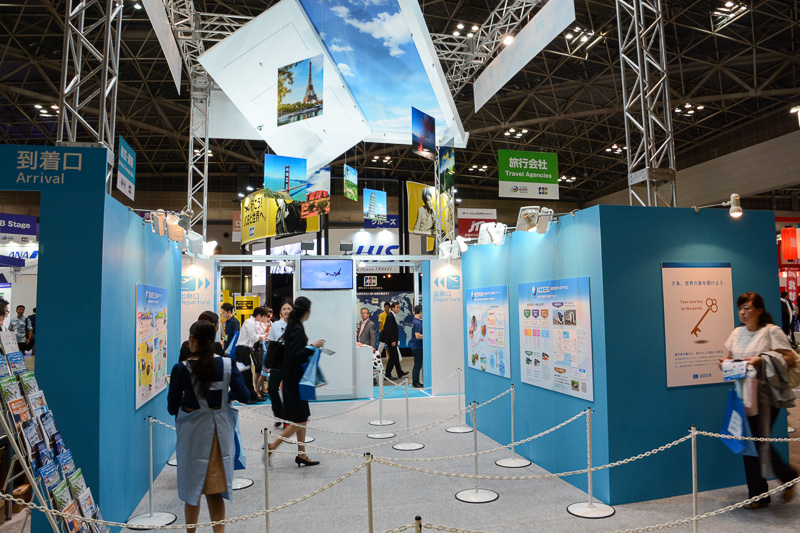 「出発口」でパスポートの説明を受けて、ツーリズムEXPOジャパンという旅へ出るイメージの成田空港ブース
