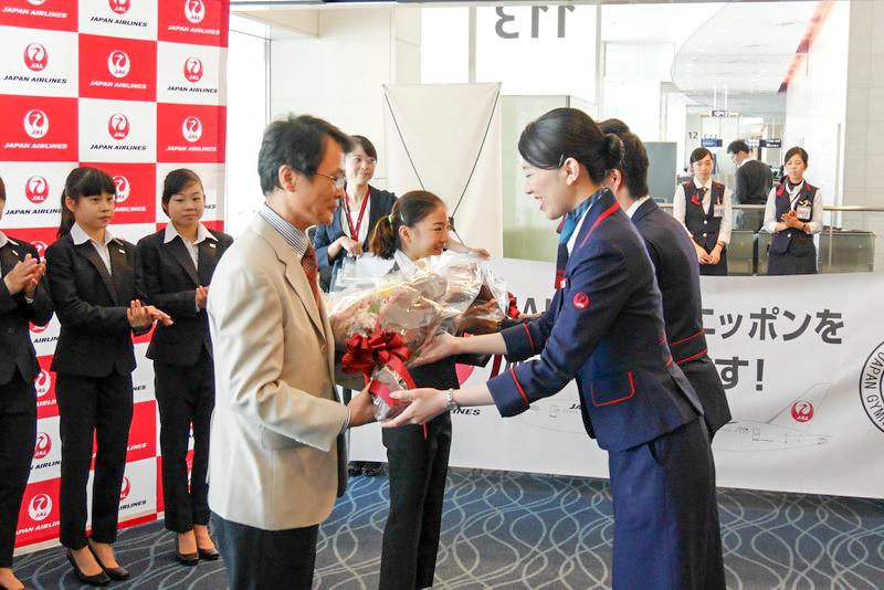 JALの係員が、体操女子日本代表ヘッドコーチの坂本周次氏(左)と選手代表の寺本明日香選手(奥)に花束を贈呈