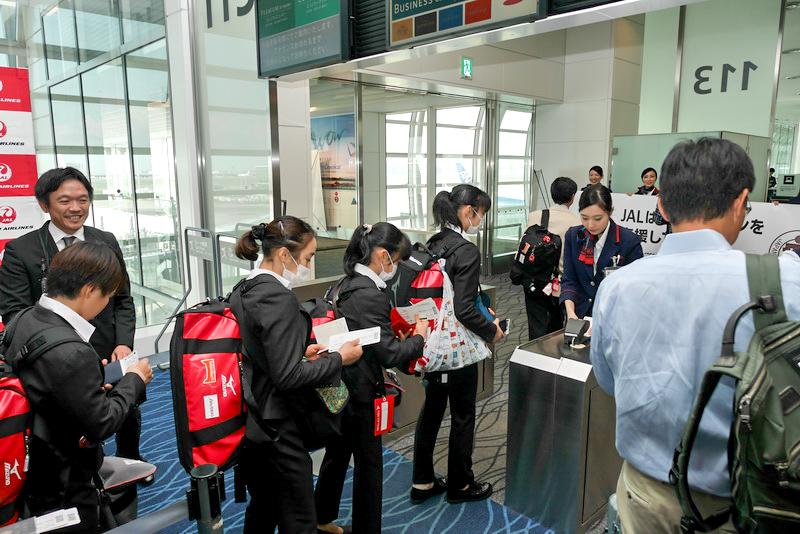 搭乗する体操女子日本代表選手団。JAL地上係員や乗客から応援の声があがっていた