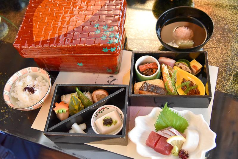「美山つづら弁当」はつづら内に2段の重箱が入っており、琵琶湖のイサザを使った小鉢や、ご当地食材である赤蒟蒻と近江牛の佃煮を始め、郷で作られた野菜を使ったメニューがたっぷり。魚三種盛りや季節の野菜なども付く。