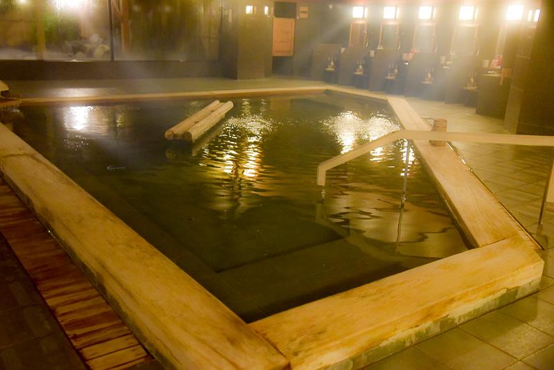 大浴場「ばんからの湯」。中央には木台があり、頭を乗せてゆったりと手足を伸ばして湯船が満喫できる。低張性アルカリ低温泉の湯は美肌効果や疲労回復、冷え性、神経痛や筋肉痛に効く