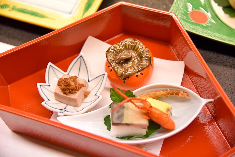柿の器に入った長芋イクラ和えはひんやりした長芋のシャキシャキとした食感とイクラのプチプチ感が楽しめる。霊余子カステラ、公魚変わり揚げ、琵琶湖産手長海老、小袖寿司は湖の幸を満喫。胡桃豆腐野菜味噌かけはもっちりな豆腐と濃厚な味噌で小さいながらも後引く美味しさ