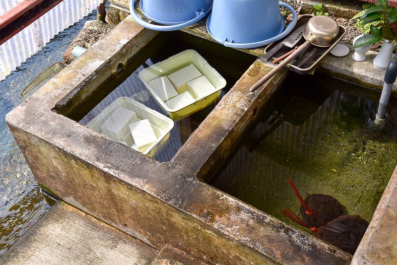 立ち寄った上原豆腐店では、壷池にできたての豆腐が湧き水に沈んでいた。各家庭でも野菜などを入れており、冷えすぎず味が分かりやすい温度とのことだ
