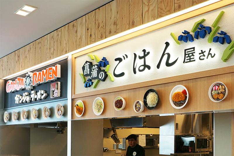 「GANJA RAMEN」と「菖蒲のごはん屋さん」が入る。看板下にメニューサンプルが立体的に付いている