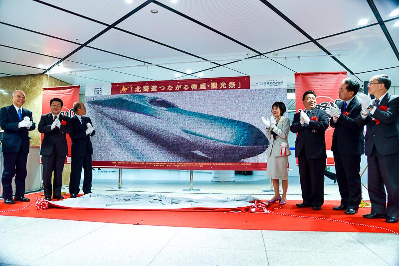 写真で生み出されたモザイクアート。北海道新幹線の車体が描かれているが、近づくとキュンちゃんやどこでもユキちゃんとともに写る人々の笑顔が見える