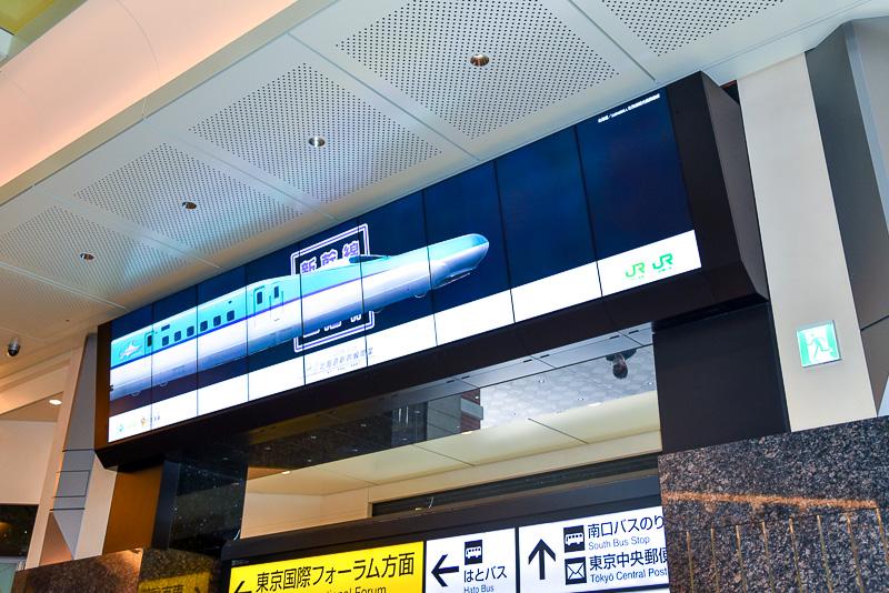 """丸の内北口の""""TOKYO MARU-VISION""""では北海道新幹線が画面上を走る横長のデイスプレイを活かした映像も放映中"""