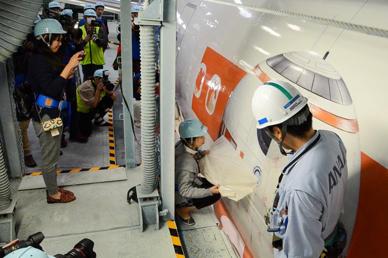 機体に貼られたBB-8のデカールから、保護シートを剥がす作業を参加者が体験