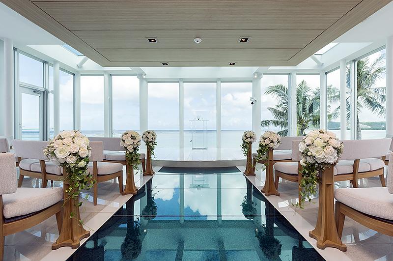 長さ8mのブルーのガラスを敷いたバージンロードの先に祭壇がある。3方をガラスに囲まれ、天井もガラスを大胆に配置。グアムの光をふんだんに採り入れたデザイン