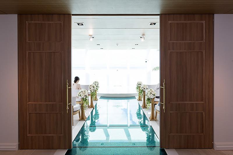 チャペルに入る瞬間を再現。扉が開くと、そこには長さ8mのバージンロードが現われる。この海のようなバージンロードを歩いて祭壇へと向かう