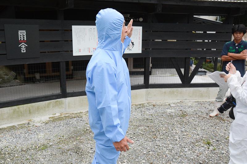 防疫のために見学する人もこんな格好に。写真のモデルは深川養鶏農業組合 黒かしわ・地どり推進部 部長の長尾英樹氏