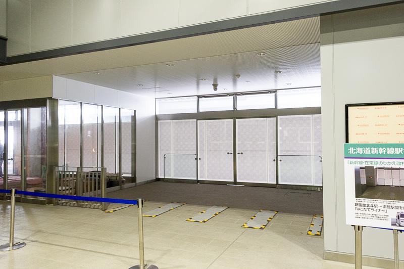 11番線の乗り換え改札。まだ改札機は設置されていないが扉の向こうはすぐ在来線の1番線・2番線ホームとなっている
