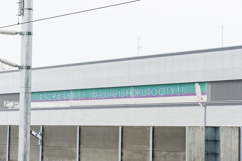 駅の脇に建設された立体駐車場の外壁には乗客を出迎えるように「ようこそ北斗市へ!!」の文字