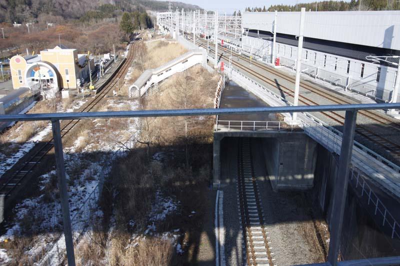 通路から青函トンネル方向の眺望。左の単線と小さなホームが隣接するJR東日本津軽線の津軽二股駅。旧津軽今別駅へ上がる屋根付きの階段通路は閉鎖され、在来線のホームも撤去されている。手前からトンネルに入るのは保守基地への引き込み線。狭軌と標準軌の三線軌条となっている