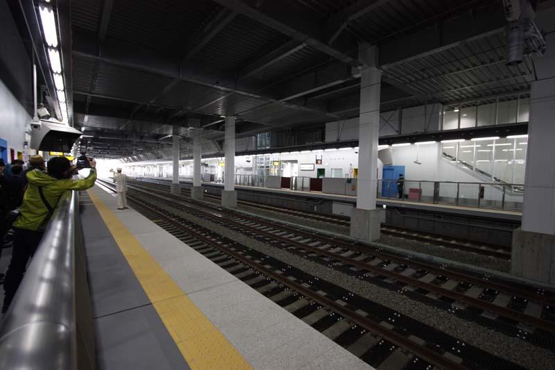 11番線、新青森・東京方面ホームから対向ホームを望む。中央の線路は下り用の通過線。またホームにあるドア等のカラフルな色は地元の伝統芸能の衣装をイメージ