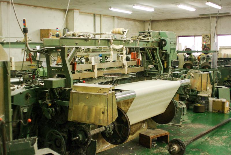 工場内の機械による機織りの様子