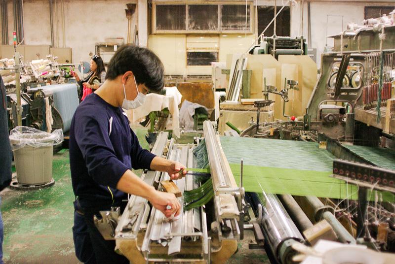 機械と職人の手によって布が作られていく