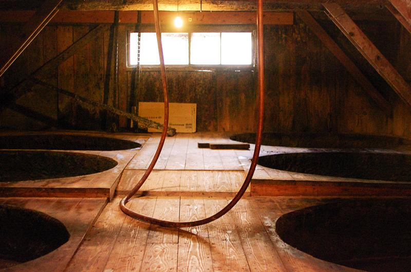 醤油の発酵のための蔵。樽が床に埋め込まれた状態で並んでいる
