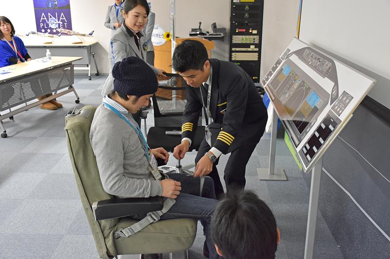 副操縦士役の参加者にシートベルトを付ける松本機長