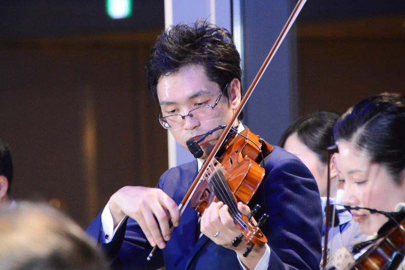 バンドマスターを務めている崔竜さん。ヴァイオリンを演奏