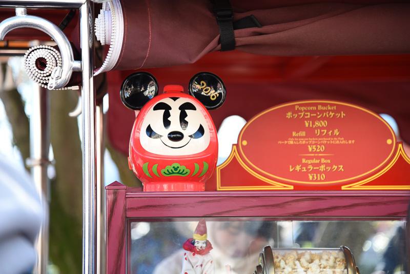 ミッキーマウスのイヤー部分に2016のロゴ入り。縁起のよい真っ赤なだるまにミッキーマウスのスマイルで今年はよい年になりそうな雰囲気。ストラップにも新春を感じさせる草花などのイラストが描かれている。東京ディズニーランドと東京ディズニーシーで購入できる「ポップコーン、バケット付き」(1800円)