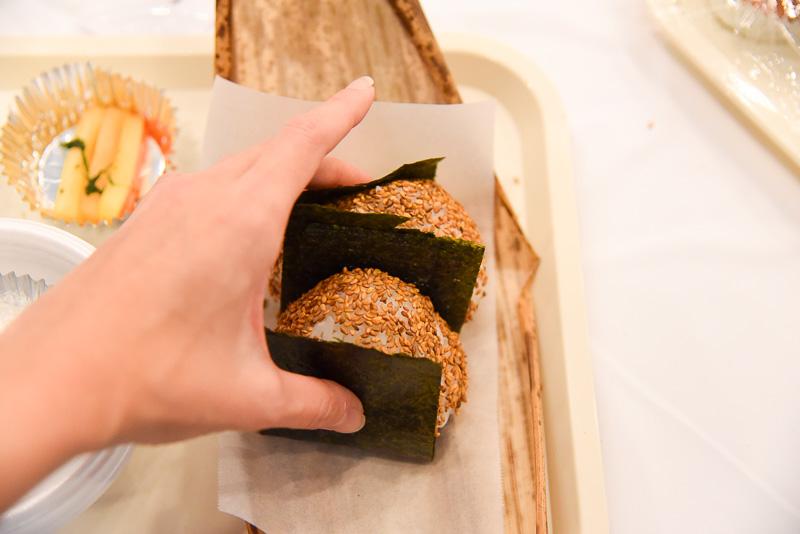 実習体験では、記者たちがおにぎりを2つつくり、竹の皮でラッピング。それを包装紙で包み手持ちできるスタイルに挑戦した