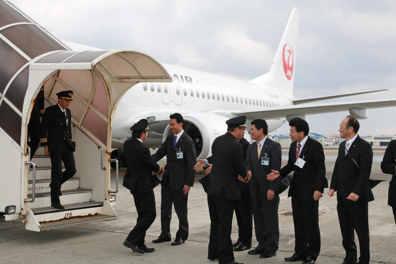 丸川社長らに出迎えられ、乗組員が沖縄の地に降り立つ