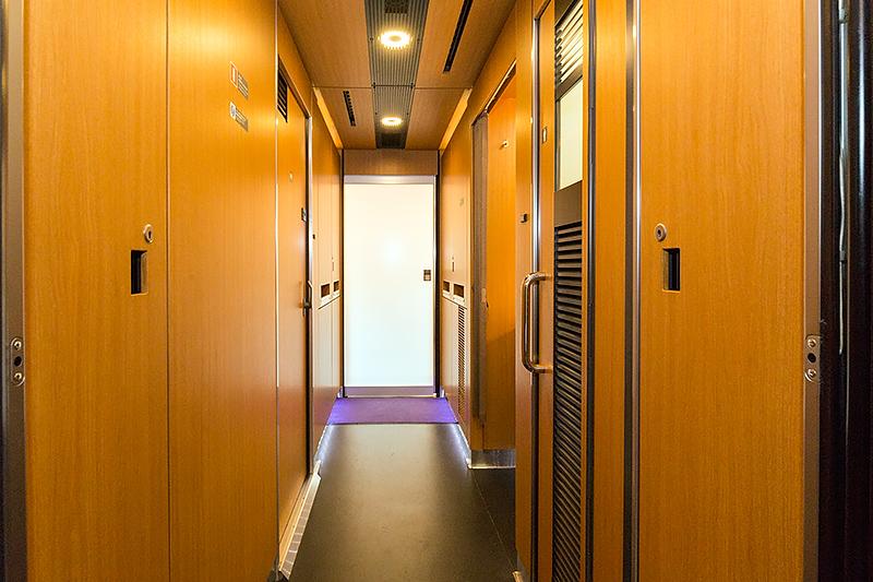 2号車のデッキから客室に向かう通路。木目調のマテリアルで統一されている