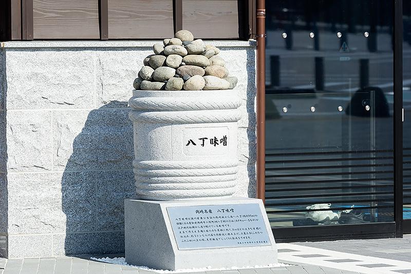 岡崎SAでは同地伝統の石工技術を活かして随所に石を利用。建物の入り口脇には八丁味噌の桶を模したモニュメントが置かれている