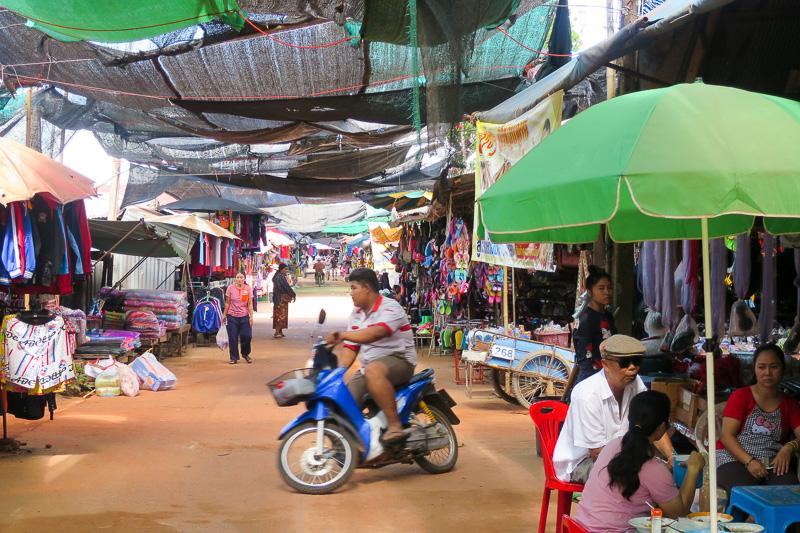 暑いので即席の屋根を貼っている商店街のような市場